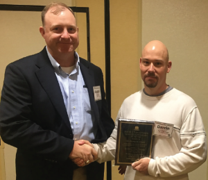 Dr. Darrin Dodds, associate Extension professor for Mississippi State University, accepts his award from Dr. Russell Nuti, cotton development specialist for PhytoGen.