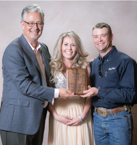 Monty Christian, (left) Bayer cotton marketing director, congratulates Mandie and Vance Smith for producing the highest gross loan value and highest yield – 7.7 bales per acre.